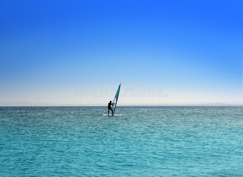 Surfer on blue sea under sky