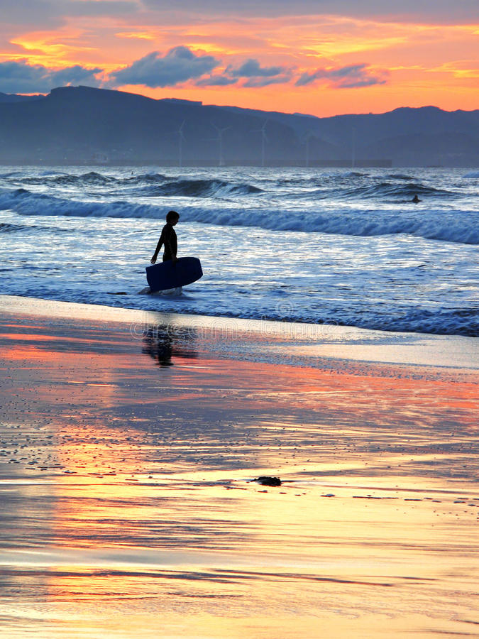 Surfer with boogie board at sunset