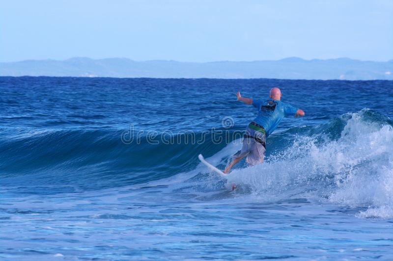 Surfer catching a small wave at Stradbroke Island royalty free stock images