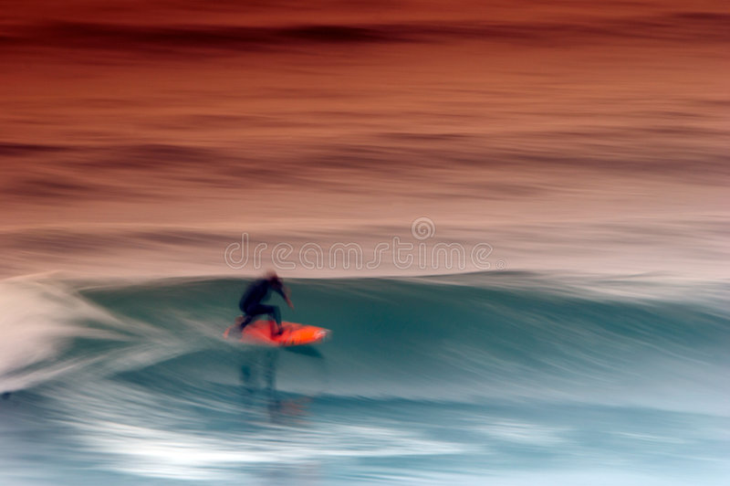 Surfer catching the wave stock image