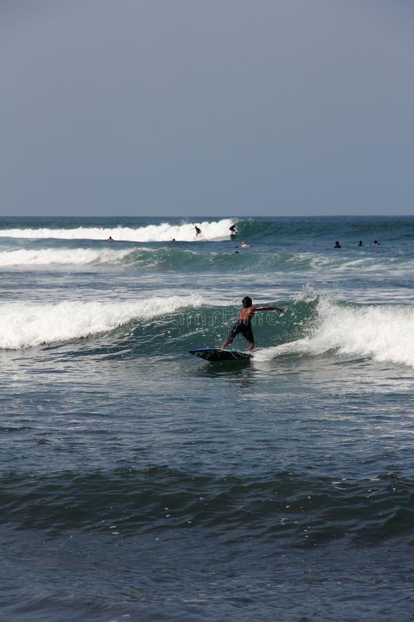 Surfer dans Bali Le garçon font surfer sur des vagues Quelques surfers sont nearb photos stock