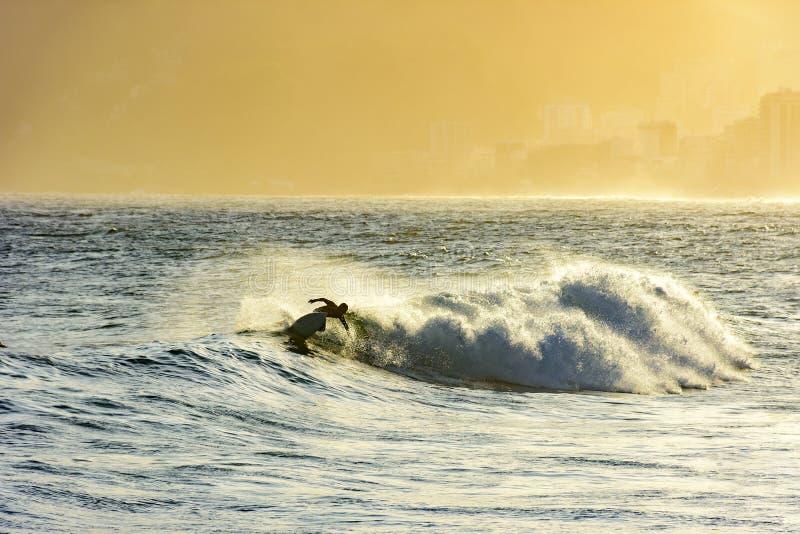 Surfer dans la vague au coucher du soleil photographie stock