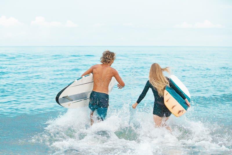 Surfer an den lächelnden Paaren des Strandes von den Surfern, die Spaß im Sommer schwimmen und haben Extremes Sport- und Ferienko lizenzfreie stockbilder