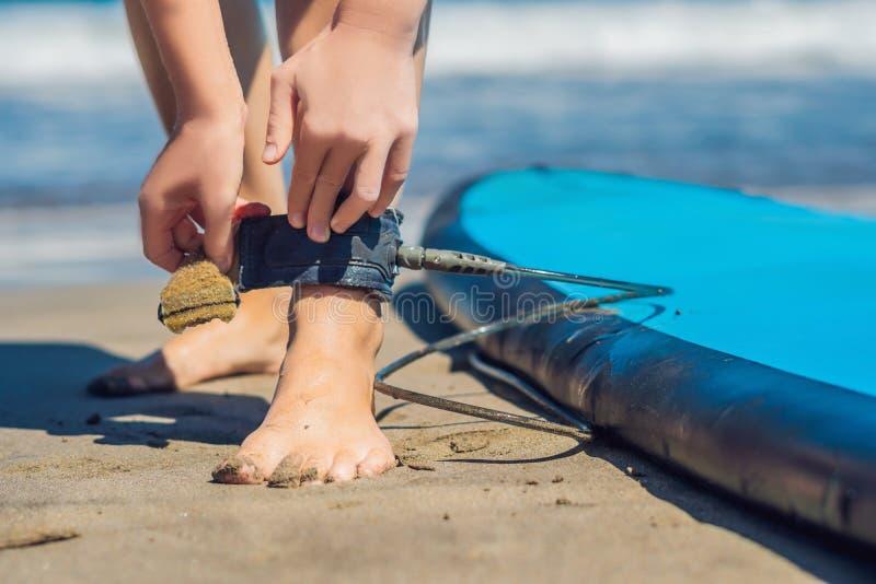 Surfer der jungen Frau, der auf der Surfbrett ` s Leine erhält stockfoto