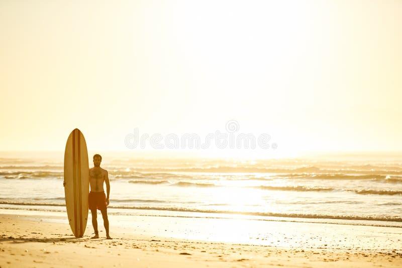 Surfer, der mit seinem Surfbrett aufrecht neben ihm auf Strand steht lizenzfreie stockbilder