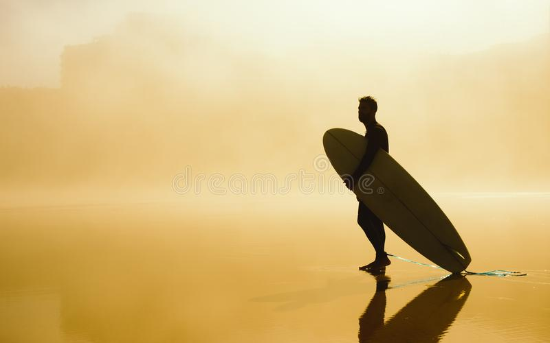 Surfer, der sein Surfbrett auf einem nebelhaften städtischen Strand hält lizenzfreie stockbilder