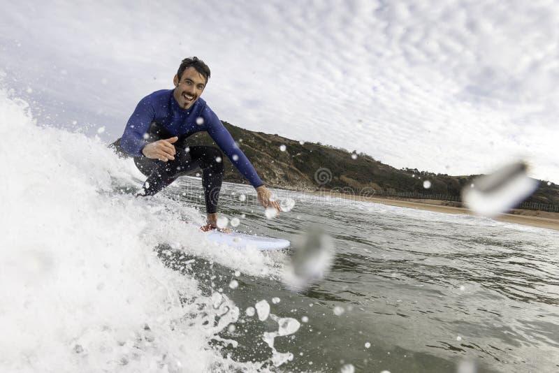 Surfer die pret hebben die een golf en het begroeten vangen stock foto's