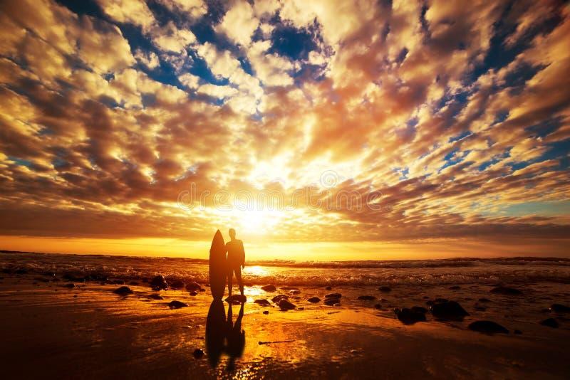 Surfer die zich met zijn surfplank op het strand bij zonsondergang over de oceaan bevinden royalty-vrije stock foto