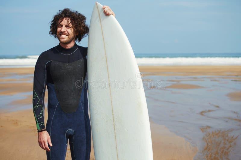 Surfer die zich op het strand met mooie oceaanhorizon op achtergrond bevinden stock afbeelding