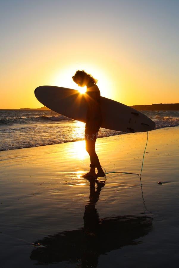 Surfer-Surfer-en bij zonsondergang stock foto's