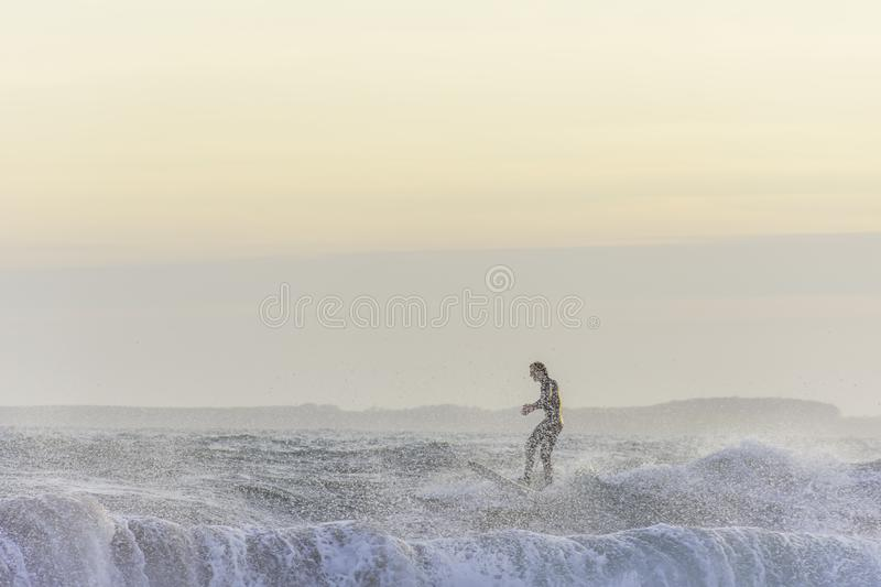 Surfer enjoying evening surf in rough sea at sunset getting splashed by water stock photo