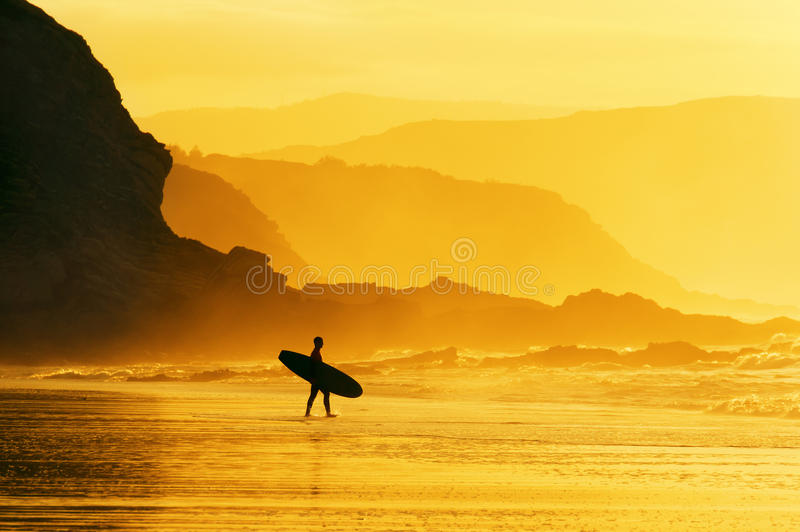 Surfer entering water at misty sunset stock photos