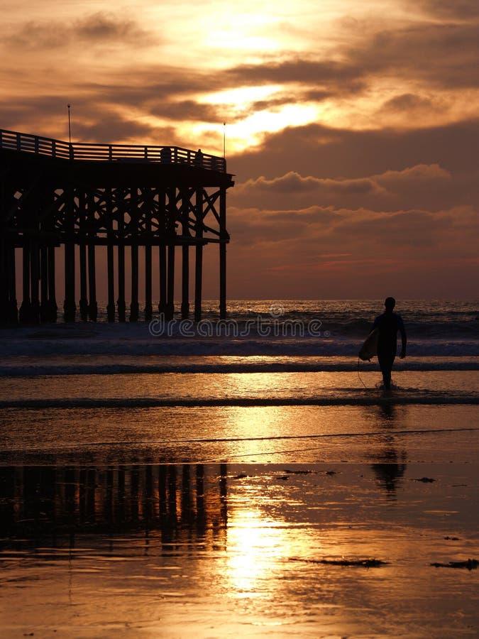 Surfer entrant dans le coucher du soleil images stock