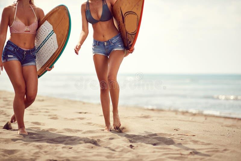 Surfer gelukkig meisje die met raad op het zandige strand lopen royalty-vrije stock afbeelding