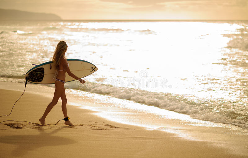 Surfer girl 5. A Beautiful woman walking with surfboard on a beach with waves breaking in the background 3