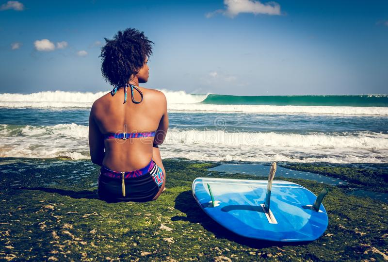 Surfer girl with afro hairstyle sitting next to blue surfboard on the green coral reef stock photography