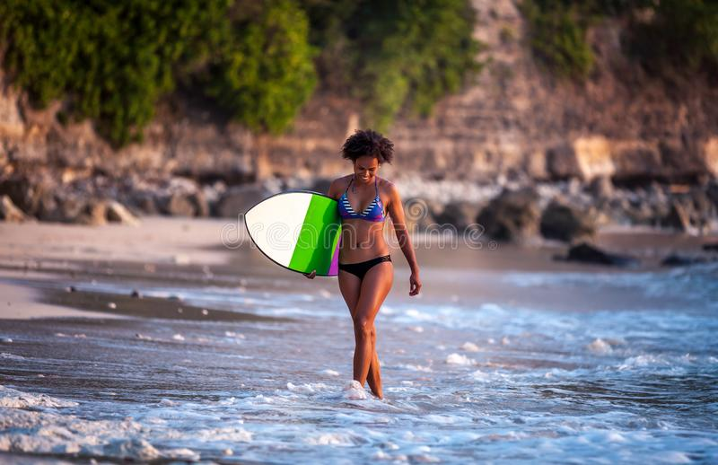 Surfer girl with afro hairstyle walking with surfboard stock images