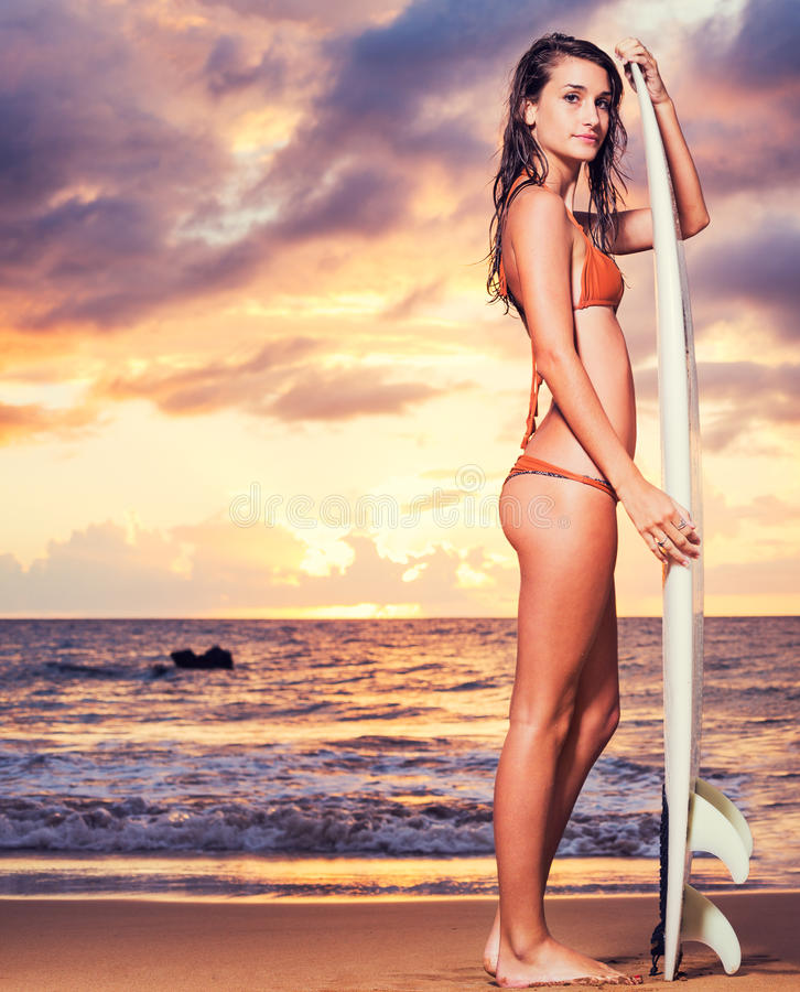 Surfer Girl on the Beach at Sunset stock photo
