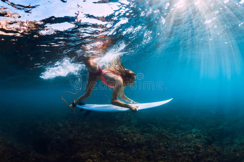 Surfer girl in bikini with surfboard dive underwater with under barrel ocean wave. Surfer girl in bikini with surfboard dive underwater with under barrel wave royalty free stock photos