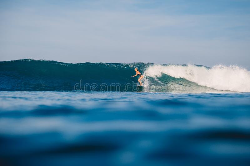 Professional surf girl at surfboard ride on barrel wave. Woman at wave royalty free stock photography