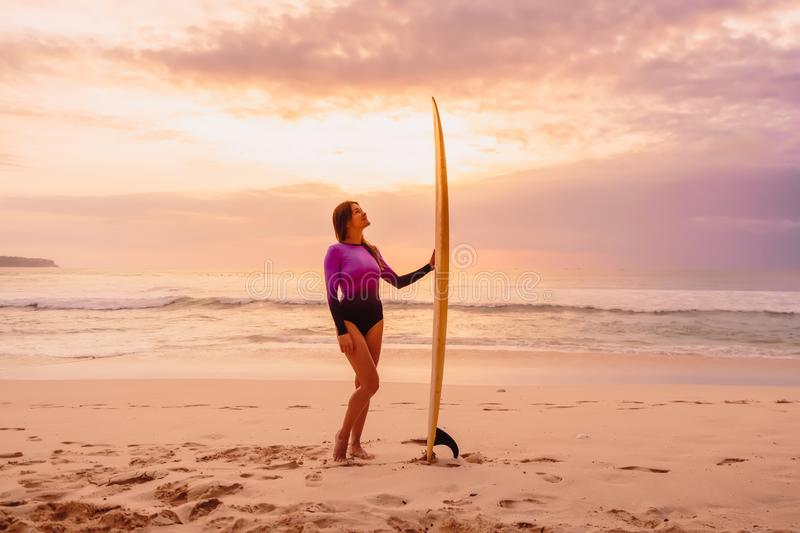 Surfer girl posing with surfboard at beach with sunset light royalty free stock image