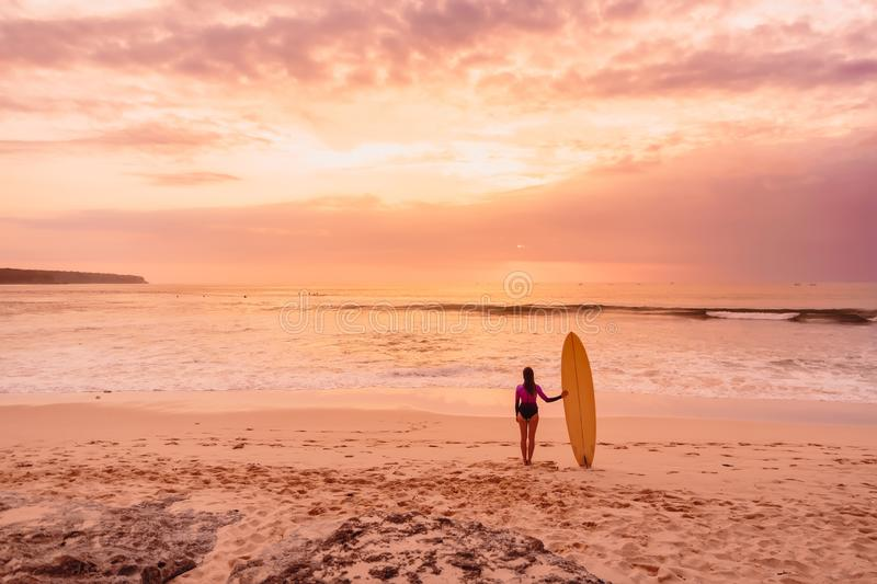 Surfer girl with surfboard at beach. Surfer woman with sunset or sunrise colors. Surfer girl with surfboard at beach. Surfer woman with sunset or sunrise royalty free stock photography
