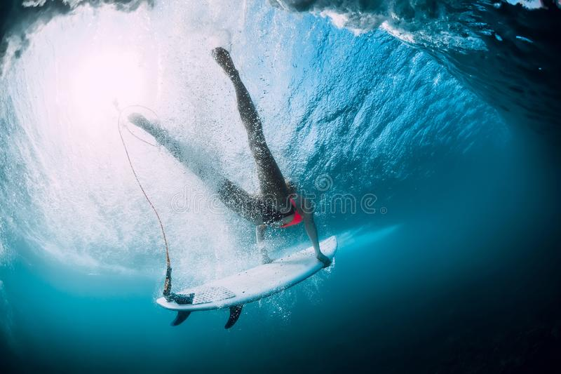 Surfer girl with surfboard dive with under ocean wave. Underwater view. Surfer girl with surfboard dive with under ocean wave stock image