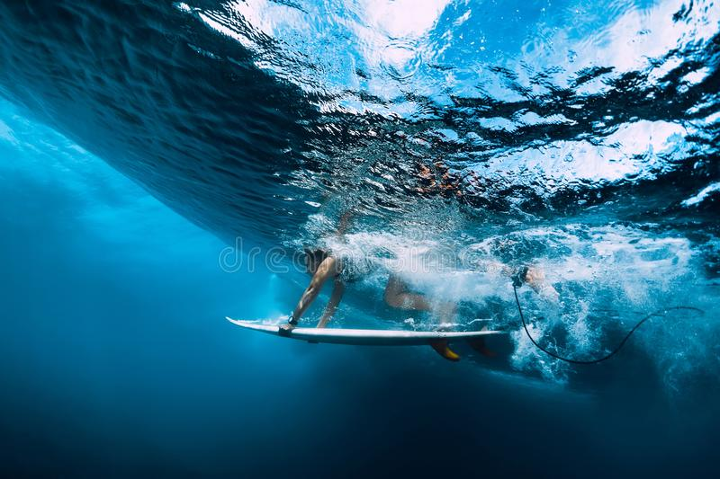 Surfer girl with surfboard dive underwater with fun under big ocean wave royalty free stock photography