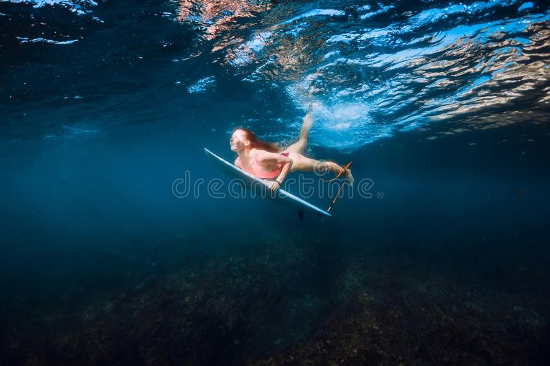 Surfer girl with surfboard dive underwater in ocean royalty free stock photo