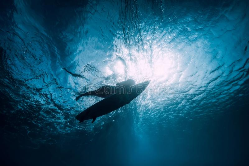 Surfer girl with surfboard dive underwater with under ocean wave. Surfer with surfboard dive underwater with under ocean wave royalty free stock images