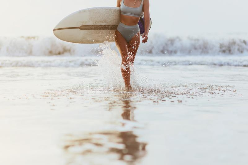 Surfer girl walking with board on the sandy beach. stock images