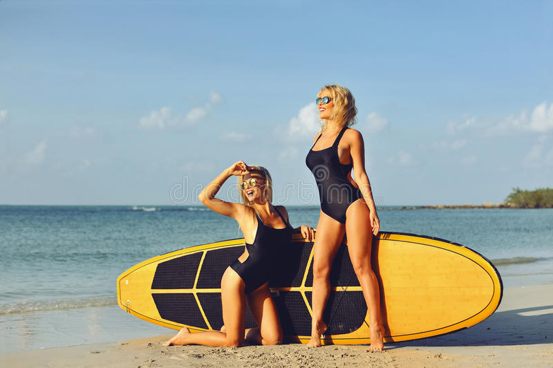 Surfer girls posing with surfboard on a beach stock photos