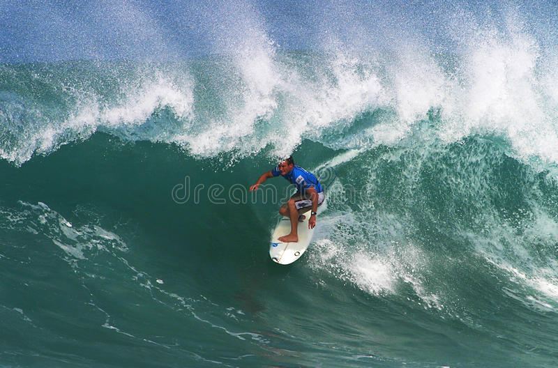 Surfer Greg Emslie Surfing at Backdoor. Photo of pro surfer, Greg Emslie, rides the tube of a wave during the Pipeline Masters surf contest, the third jewel of royalty free stock images