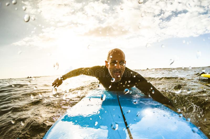 Surfer guy paddling with surfboard at sunset in Tenerife stock photography