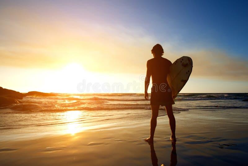 Surfer het letten op zonsondergang op het strand stock afbeeldingen