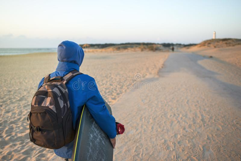Surfer wrapped in a coat walks towards the shore stock images