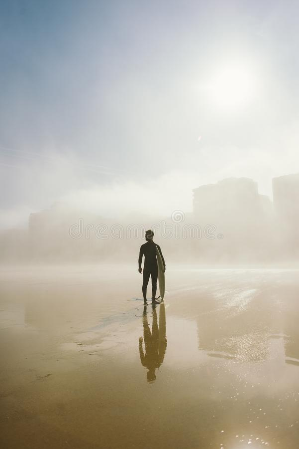 Surfer holding his surfboard on a misty urban beach royalty free stock images