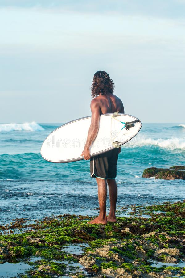 Surfer waits for a wave. The surfer is holding a surfboard on the Indian Ocean shore stock photography