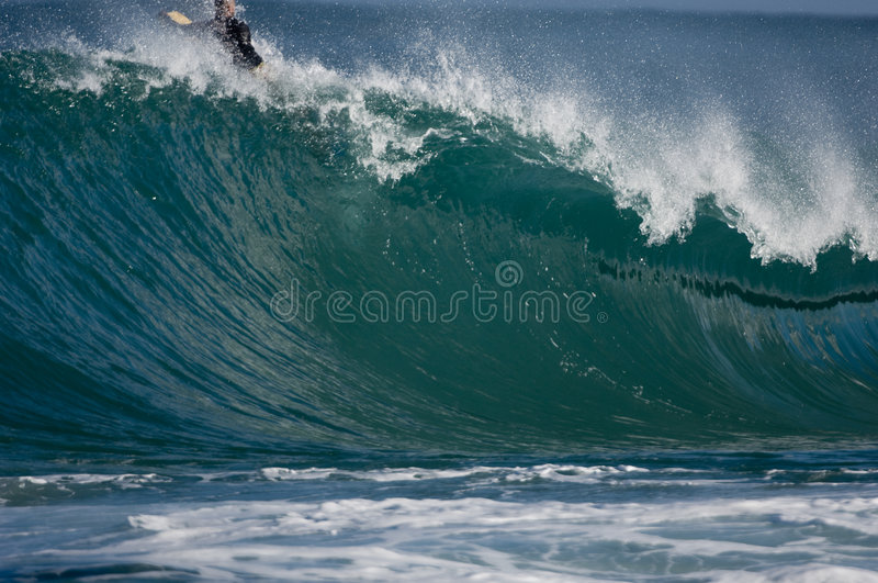 Surfer on huge wave. Surfer on top of tall breaking wave in Oahu, Hawaii royalty free stock photography