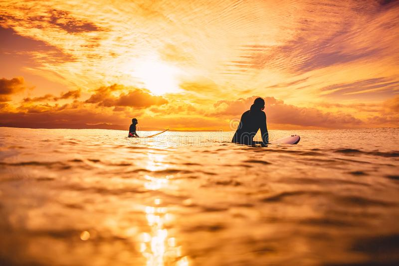 Surfer im Ozean bei Sonnenuntergang oder Sonnenaufgang Paare des Surfers und des Ozeans stockbilder