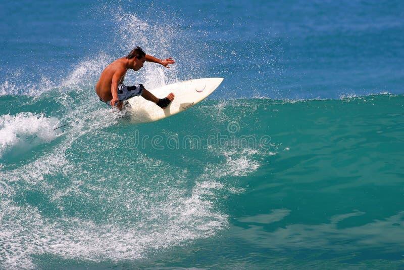 Surfer Jason Honda, die am Waikiki Strand surft stockfotos