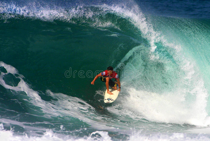 Surfer Kalani Robb Surfing at Backdoor. Photo of pro surfer, Kalani Robb, rides the tube of a wave during the Pipeline Masters surf contest, the third jewel of royalty free stock image