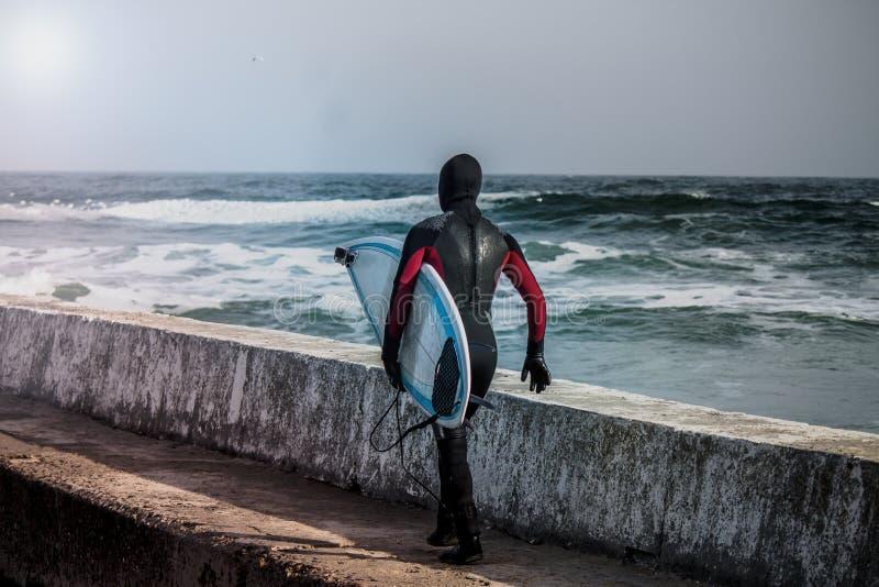 Surfer läuft in Wasser im Winter lizenzfreie stockfotos