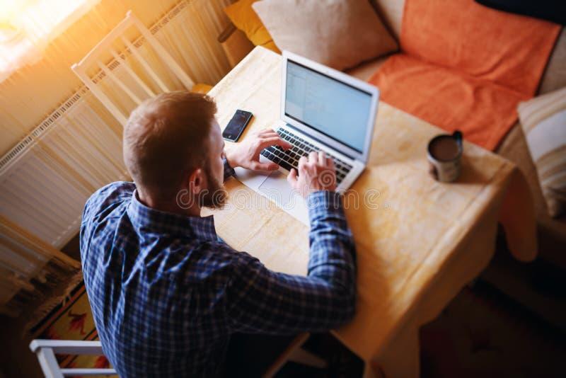 Surfer le filet dans le bureau Jeune homme sûr travaillant sur l'ordinateur portable photographie stock