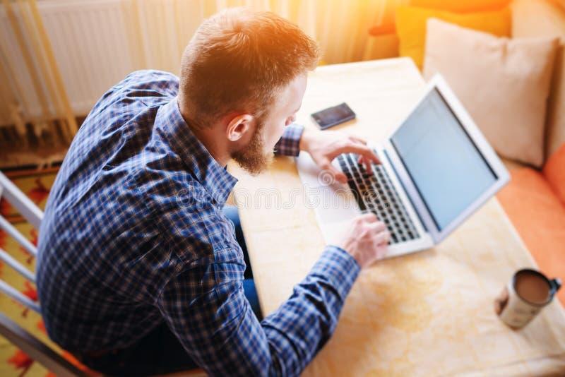Surfer le filet dans le bureau Jeune homme sûr travaillant sur l'ordinateur portable et souriant tout en se reposant à son lieu d images stock