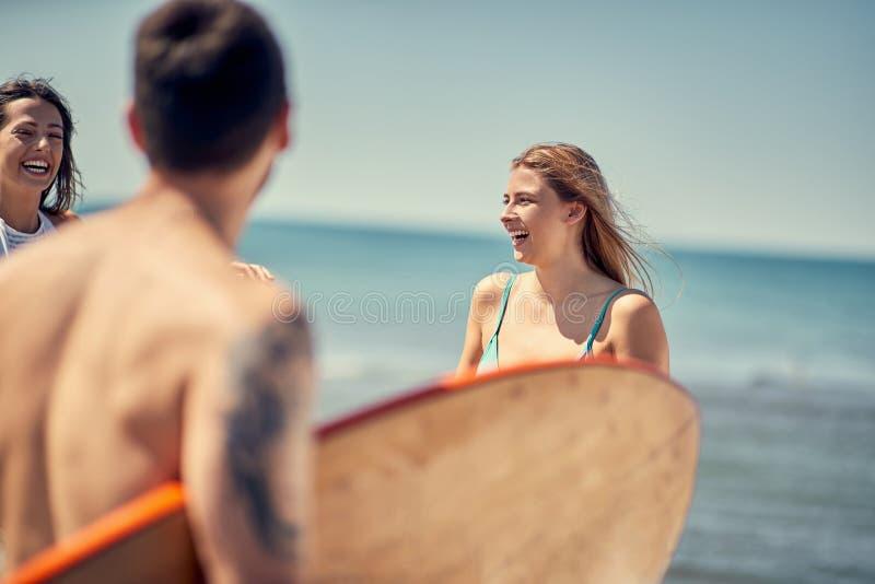 Surfer-Mädchen Sexy Frau an den sportlichen Leuten des Strandes mit Brandungsboa stockbild