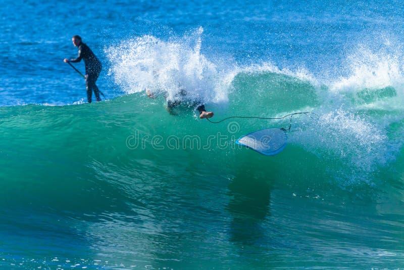 Surfer-Mädchen zusammenstoßendes Wipeout-Wellen-Surfen lizenzfreies stockfoto