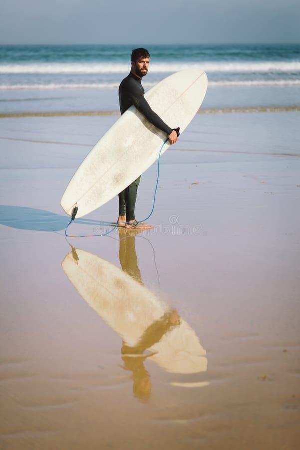 Surfer met zijn surfplank alvorens in het overzees voor surfin te krijgen royalty-vrije stock afbeelding