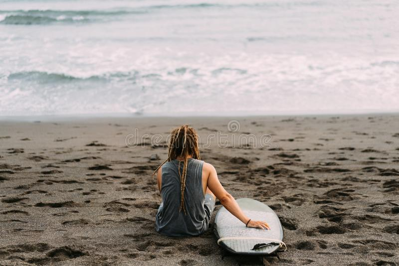 Surfer mit Dreadlocks mit surfingboard nahe Ozean stockbilder