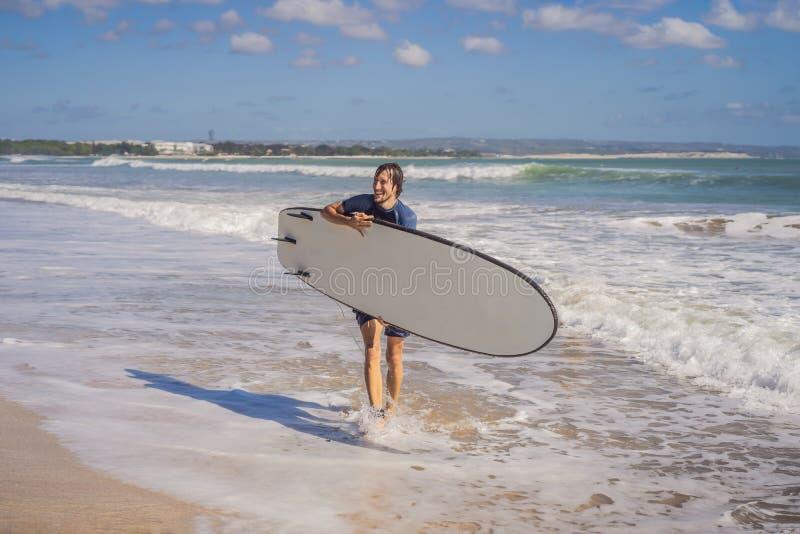 Surfer mit seinem Surfbrett, das zu den Wellen läuft stockbilder